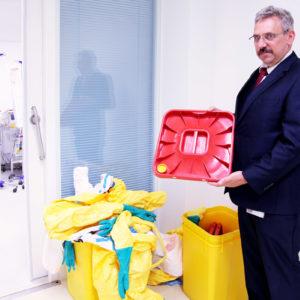 Abfallbeauftragter Hans Peter Kiefler vor einem Sammelbehälter. Deutlich zu sehen: Die kleine gelbe Öffnung im Behälterdeckel, durch die der Dampf beim Autoklavieren einströmen kann. (Foto: Abfallmanager Medizin)