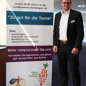 """Verwaltungsleiter Tobias Schuchardt ist ausgebildeter Klimamanager. Im Rahmen des Projekts KLIK green wird bereits vor dem Speisesaal auf die Kampagne """"Zu gut für die Tonne!"""" hingewiesen (Foto: Abfallmanager Medizin)"""